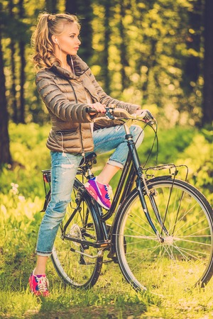 Cheerful teenage girl listens music on a bicycle outdoors photo