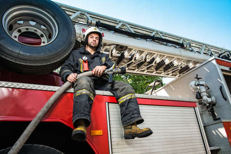 firefighting: Firefighter sitting on a firefighting truck with water hose