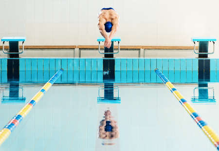 start position: Young muscular swimmer jumping from starting block in a swimming pool Stock Photo