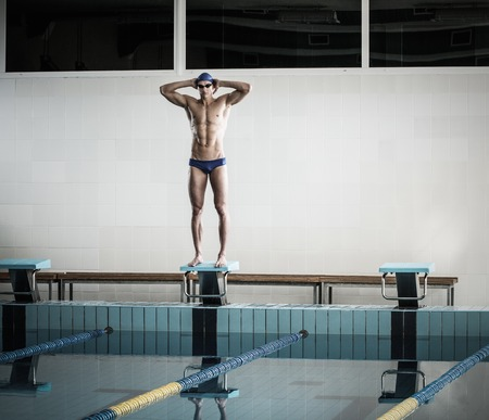 start position: Young muscular swimmer standing on starting block in a swimming pool