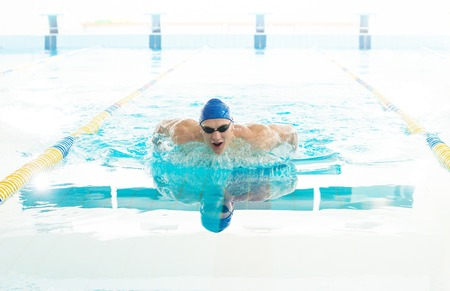 Young man in swimming cap and goggles swim using breaststroke technique  photo