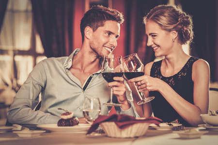 浪漫: 美麗的年輕夫婦與紅葡萄酒在豪華餐廳眼鏡