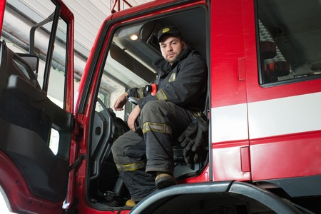 fireproof: Fireman behind steering wheel of a firefighting truck  Stock Photo