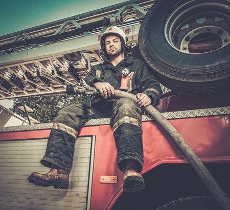 rescuer: Firefighter sitting on a firefighting truck with water hose
