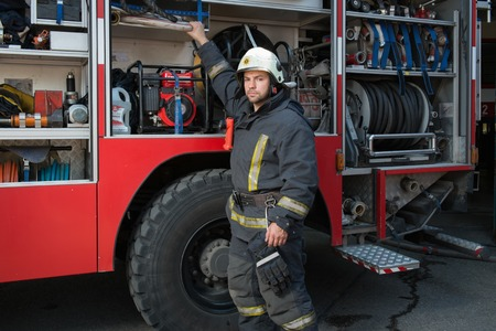 building on fire: Fireman taking equipment from firefighting truck