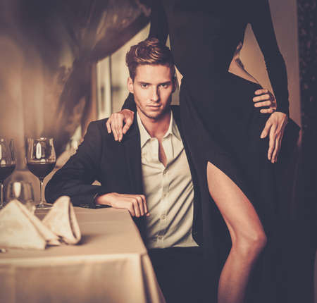 elegance: Sexy well-dressed young couple in luxury interior