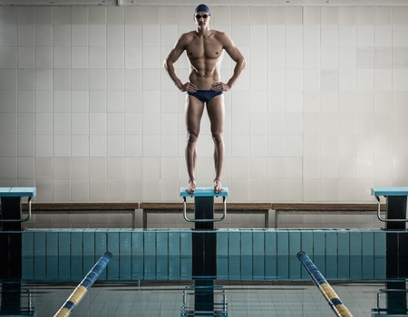 starting position: Young muscular swimmer standing on starting block in a swimming pool