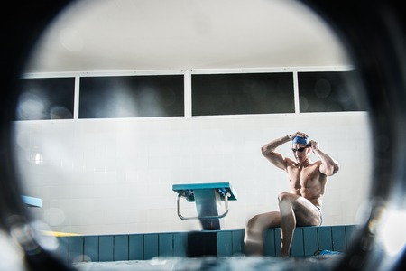 Young muscular swimmer putting on swimming goggles photo