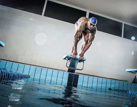 competition: Young muscular swimmer in low position on starting block in a swimming pool