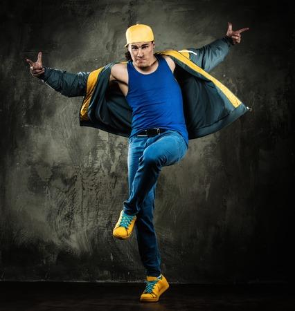 Man dancer in cap and jacket showing break-dancing moves photo
