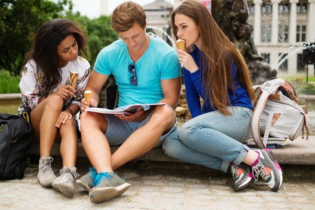 Group of multi ethnic students with ice-cream near fountain in a city park  photo