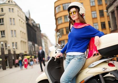 casco moto: Chica alegre joven cerca de la moto en la en la ciudad europea
