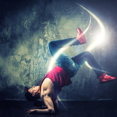 balance beam: Stylish man dancer showing break-dancing moves with magic beams around him  Stock Photo
