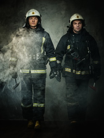 Two firefighters with axes in a smoke photo