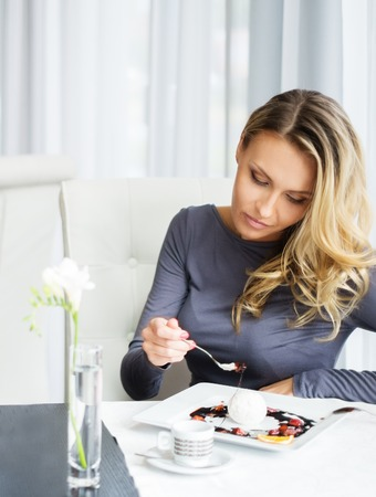 woman eating cake: Woman alone eating dessert in a restaurant