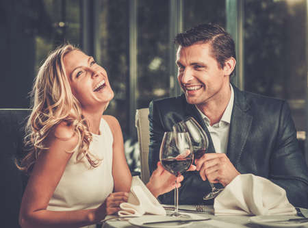 gourmet dinner: Pareja alegre en un restaurante con vasos de vino tinto