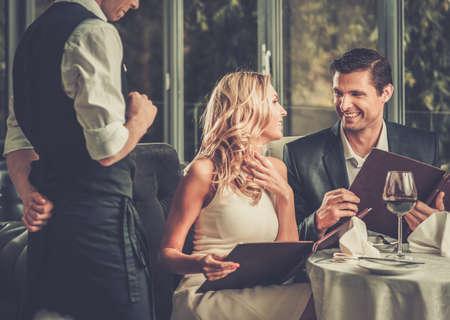 romântico: Pares alegres com menu em um restaurante tomada de ordem Imagens