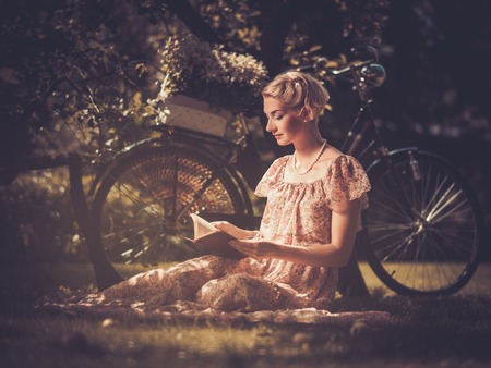 Blond retro woman with a book in summer dress sitting on a meadow photo