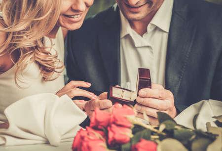 anillos de boda: Hombre que sostiene la caja con la toma de anillo proponer matrimonio a su novia Foto de archivo