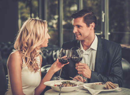 Cheerful couple in a restaurant with glasses of red wine photo
