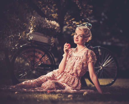Beautiful blond retro woman with an apple and bicycle behind her photo