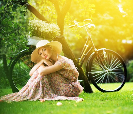 Beautiful blond retro woman with bicycle behind her photo