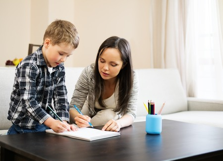 mother helping baby: Happy young mother with her son drawing in home interior