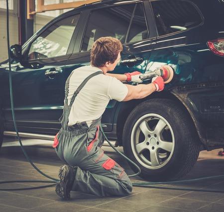 Serviceman polishing car body with machine  in a workshop photo