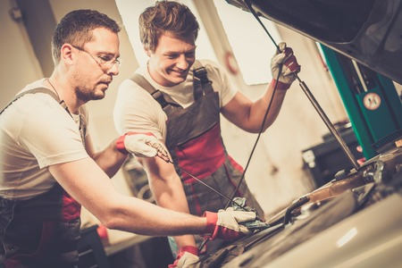 automobile workshop: Two mechanics checking oil level in a car workshop Stock Photo