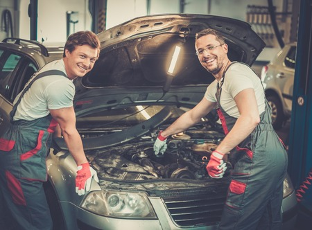 automobile workshop: Two mechanics fixing car in a workshop