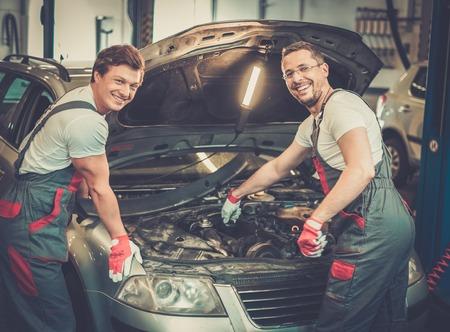 motor mechanic: Two mechanics fixing car in a workshop