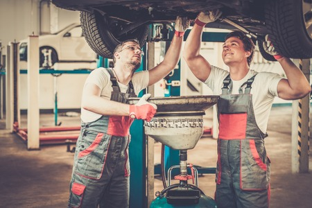 service lift: Two mechanics changing oil  in a car workshop