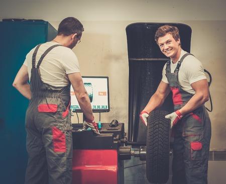 wheel balancing: Two mechanics balancing wheel in a car workshop