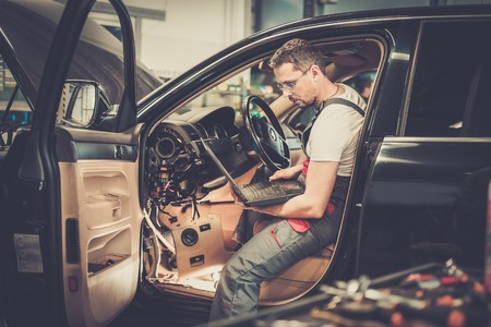 Serviceman making car diagnostics with laptop in a workshop Stock Photo