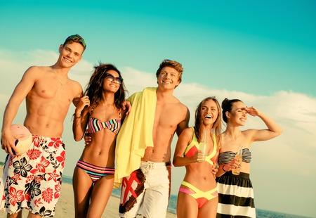 african bikini: Group of multi ethnic friends walking on a beach Stock Photo