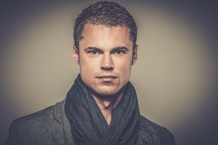 Handsome young man in casual jacket and neck scarf Stock Photo