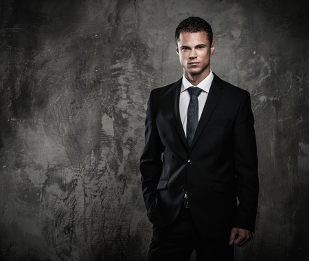 Well-dressed man in black suit against grunge wall  Stock Photo