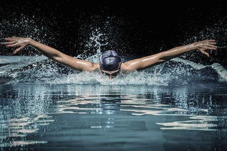 swim?: Hombre joven en el gorro de baño y gafas de natación utilizando la técnica de braza