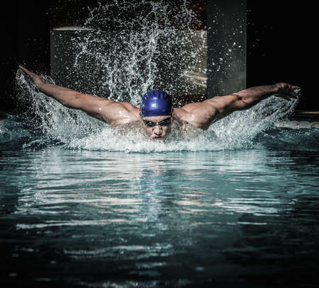 swimming: Young man in swimming cap and goggles swim using breaststroke technique