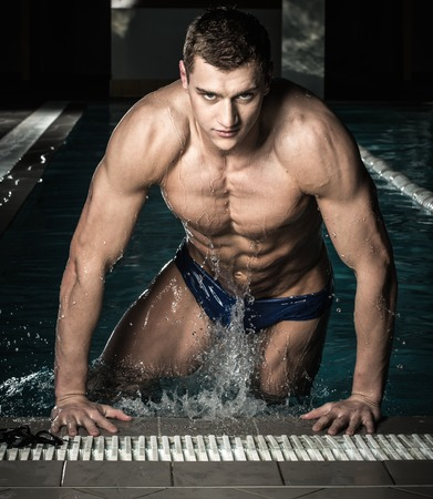 Young muscular swimmer in a swimming pool