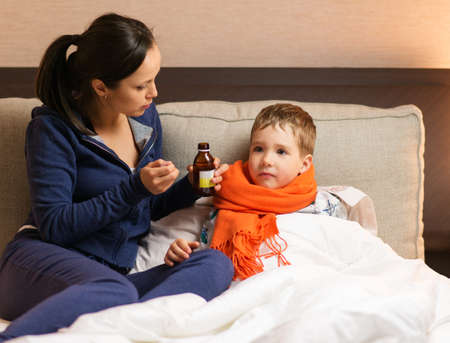 Young mother and her sick son in a bed photo