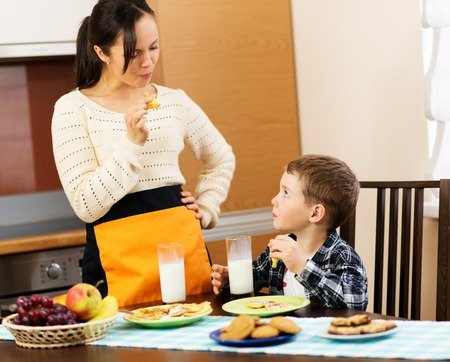 Young happy mother and her child eating healthy breakfast  photo