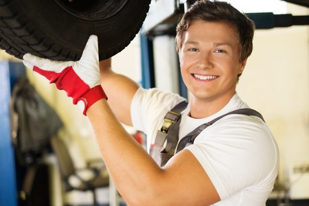 Cheerful serviceman checking suspension in a car workshop  photo