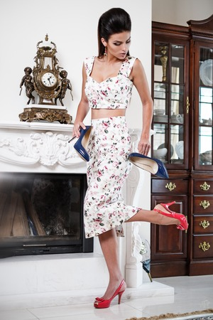 Beautiful woman choosing shoes in luxury home interior  photo