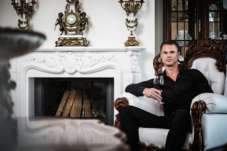 Handsome well-dressed man sitting with red wine in luxury  house interior  photo