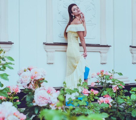 Beautiful woman in dress near luxury building facade among roses  photo