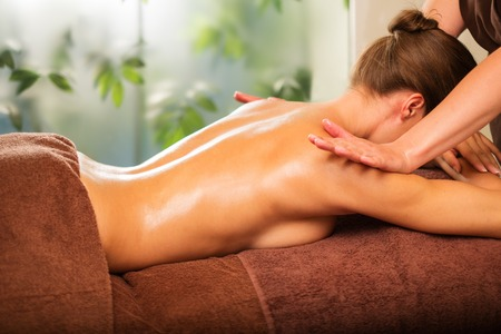 massage table: Young woman having massage in a spa salon