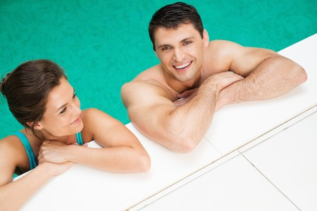 Young cheerful couple relaxing in a swimming pool photo