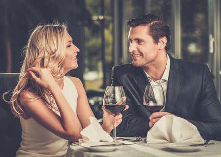 diner romantique: Enthousiaste deux dans un restaurant avec des verres de vin rouge