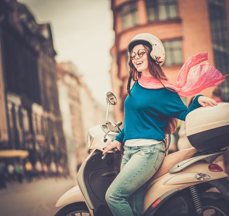 Young cheerful girl near scooter in in european city  Stock Photo